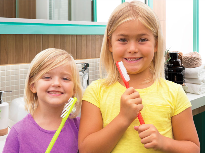 Two young girls holding giant toothbrushes.